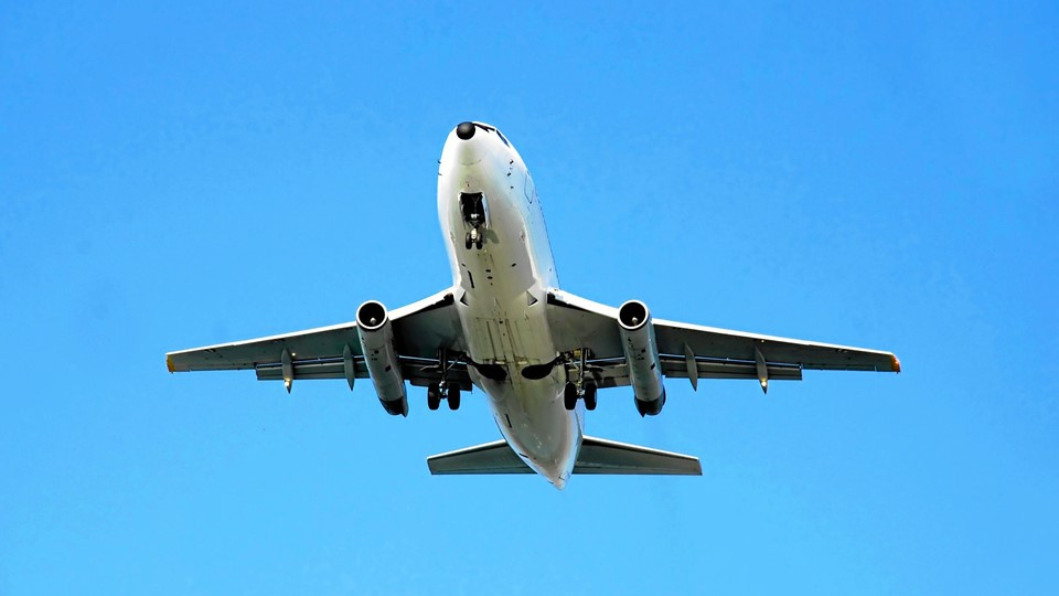 passenger airplane flying over blue sky isolated