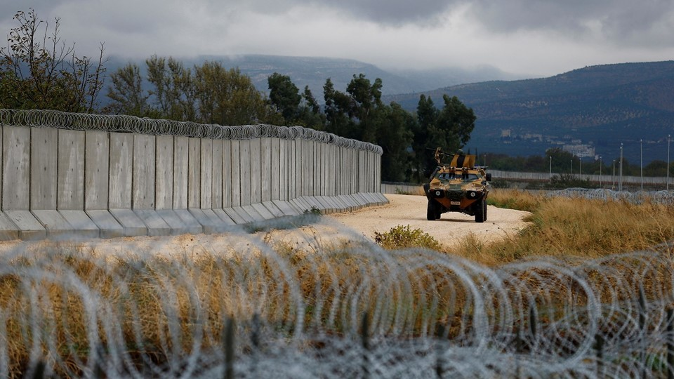 File picture of an armoured military vehicle driving past a wall along the border between Turkey and Syria, near the southeastern village of Besarslan, in Hatay province Foto: Reuters/Umit Bektas