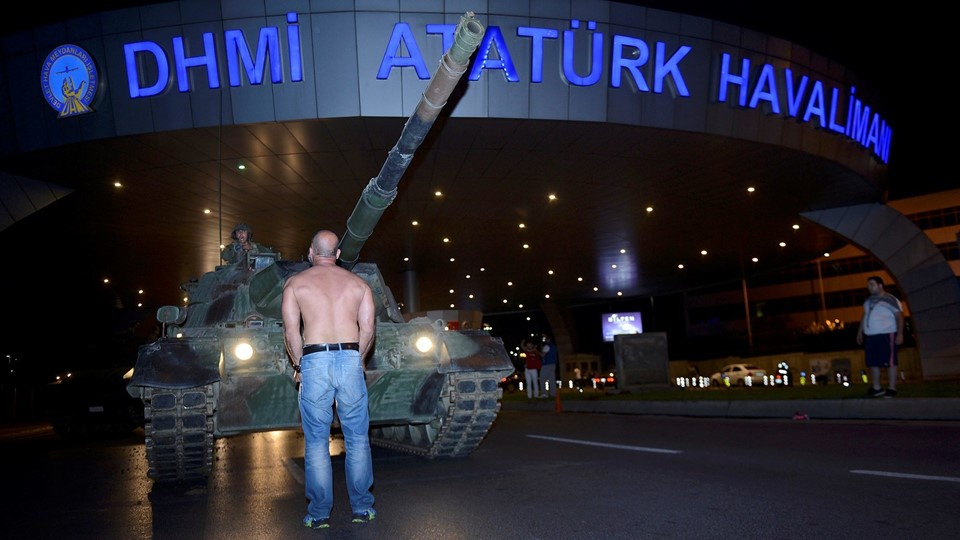 A man stands in front of a Turkish army tank at Ataturk airport in Istanbul Foto: Reuters/Stringer