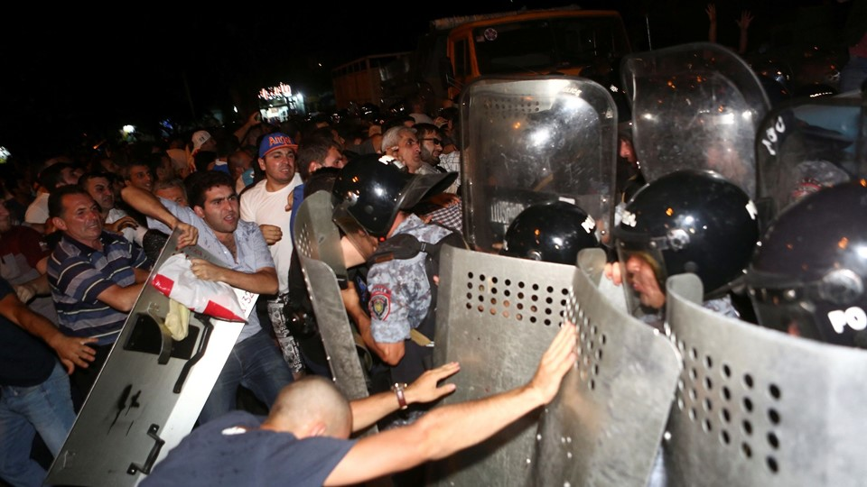 Riot police clash with demonstrators who had gathered in show of support for gunmen holding several hostages in police station in Yerevan Foto: Reuters/Handout