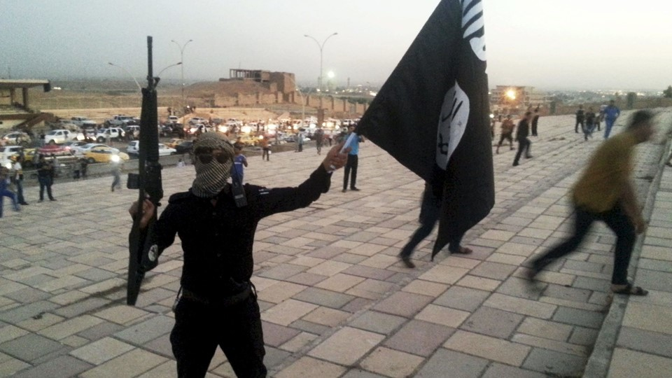 File photo of a fighter of ISIL holding a flag and a weapon on a street in Mosul Foto: Reuters/Stringer