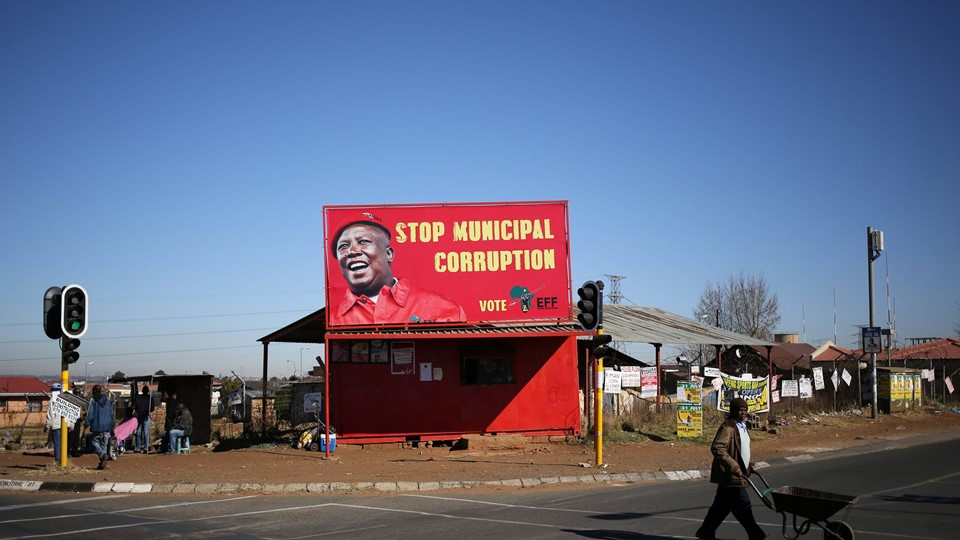 A man pushes a wheelbarrow past a billboard of the Economic Freedom Fighters (EFF), which is led by Julius Malema, Zuma's one-time protege and a former ANC youth leader, in Soweto, South Africa Foto: Reuters/Siphiwe Sibeko