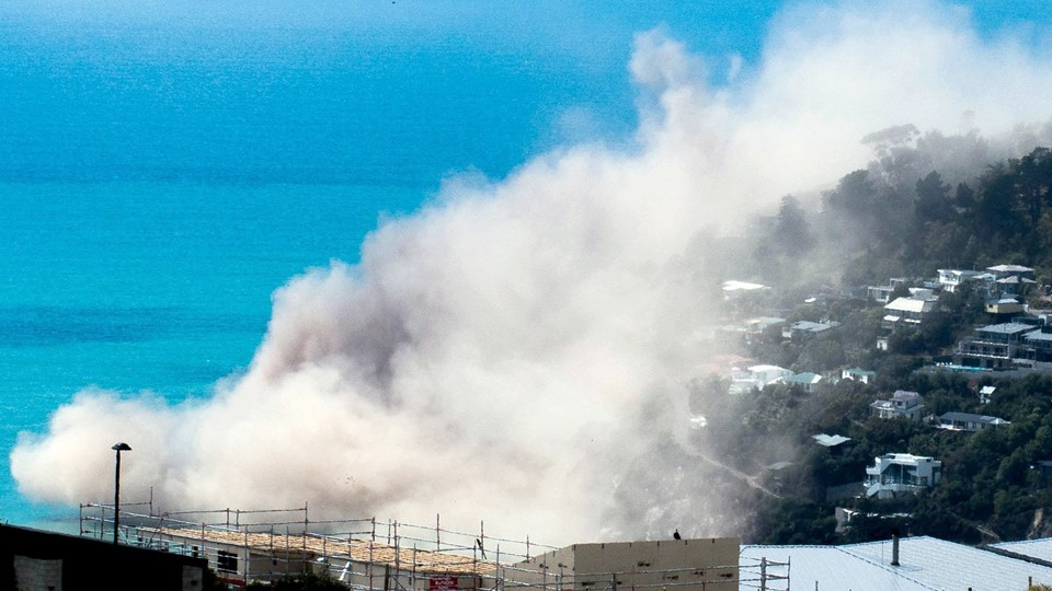 Dust and debris rise above houses after a cliff collapsed due to an earthquake on the Whitewash Head area, located above Scarborough Beach in the suburb of Sumner, Christchurch, New Zealand Foto: Reuters/Handout