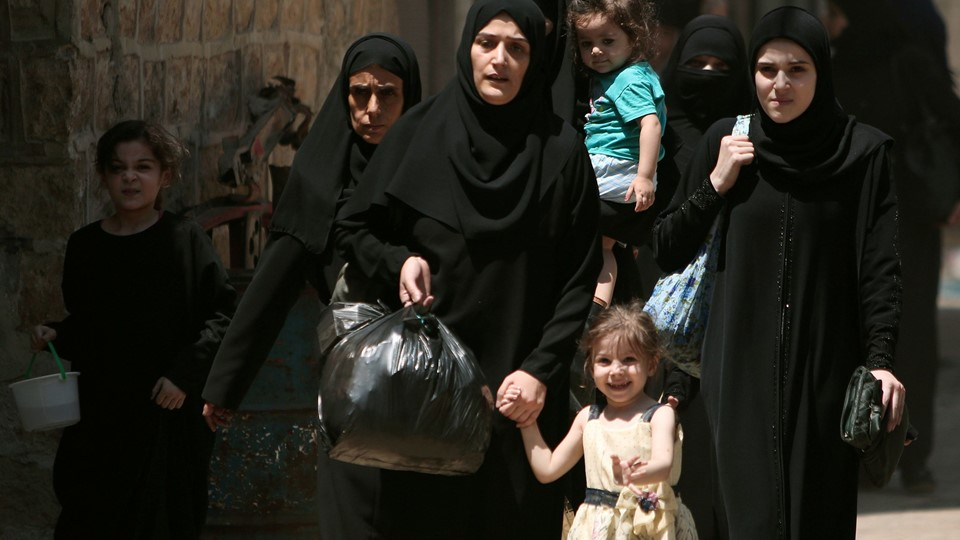 Women and children carry belongings and they flee towards safer parts of Manbij city Foto: Reuters/Rodi Said