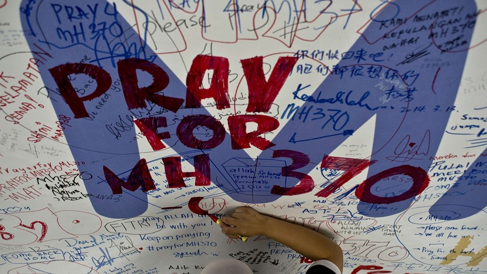 """TOPSHOTS  A Malaysia Airlines employee writes a message expressing prayers and well-wishes for passengers onboard missing Malaysia Airlines (MAS) flight MH370 at Kuala Lumpur International Airport in Sepang on March 14,       2014. The needle-in-a-haystack hunt for the missing Malaysian airliner spread to the vast Indian Ocean after the White House cited """"new information"""" that it might have flown for hours after vanishing nearly seven days ago.    AFP PHOTO/ MANAN VATSYAYANA"""