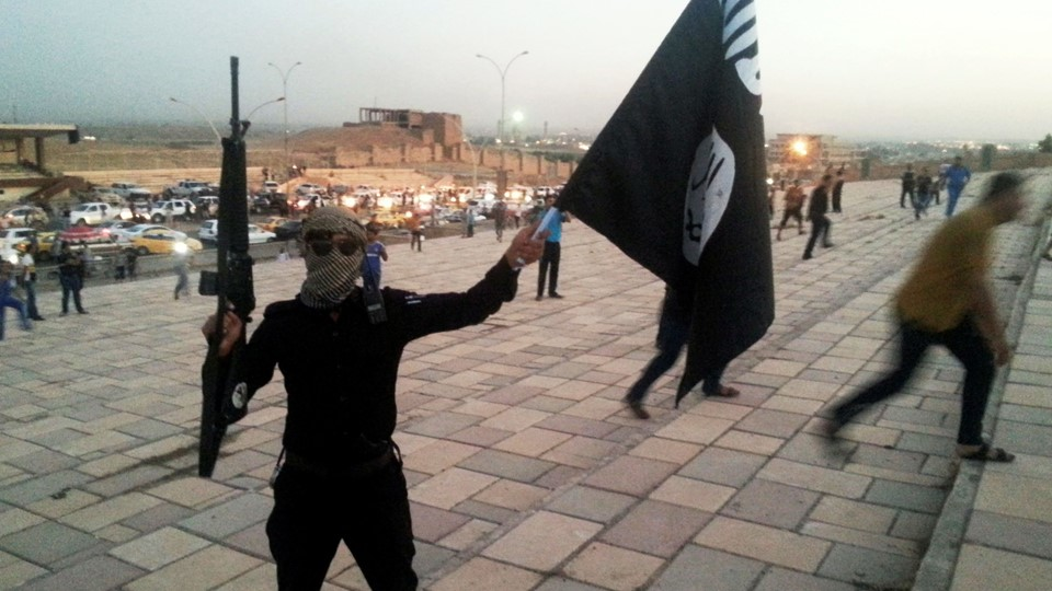 A fighter of the ISIL holds a flag and a weapon on a street in Mosul Foto: Reuters/Stringer