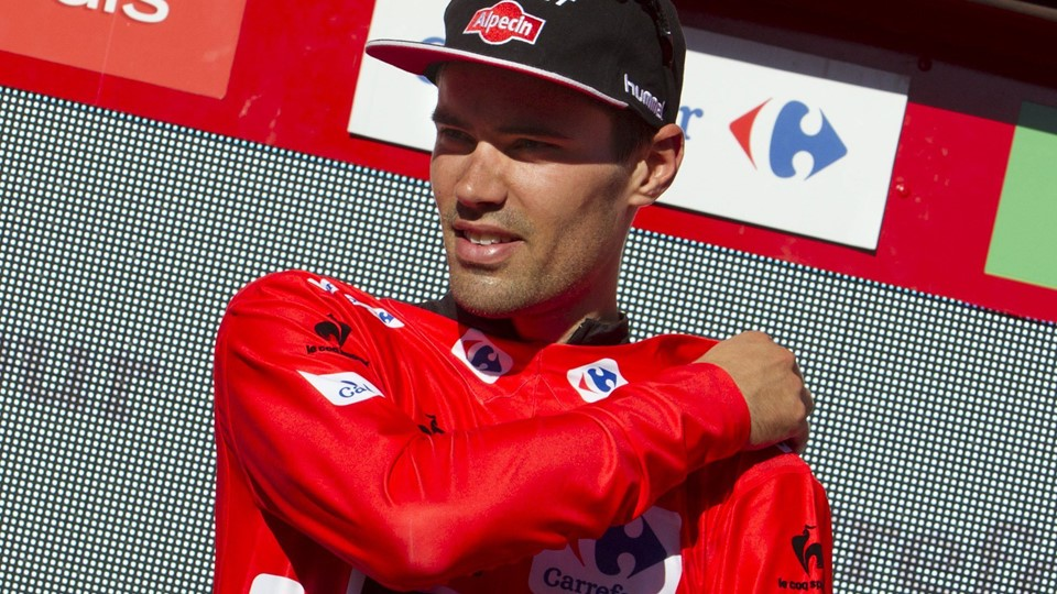 Giant-Alpecin's Dutch cyclist Tom Dumoulin puts on the red jersey on the podium after the18th stage of the 2015 Vuelta Espana cycling tour, a 204 km route between Roa and Riaza on September 10, 2015. Ireland's Nicholas Roche claimed the 18th stage of Spain's Vuelta on Thursday as Dutch rider Tom Dumoulin maintained his three second advantage over Italian Fabio Aru in the overall standings. AFP PHOTO / JAIME REINA