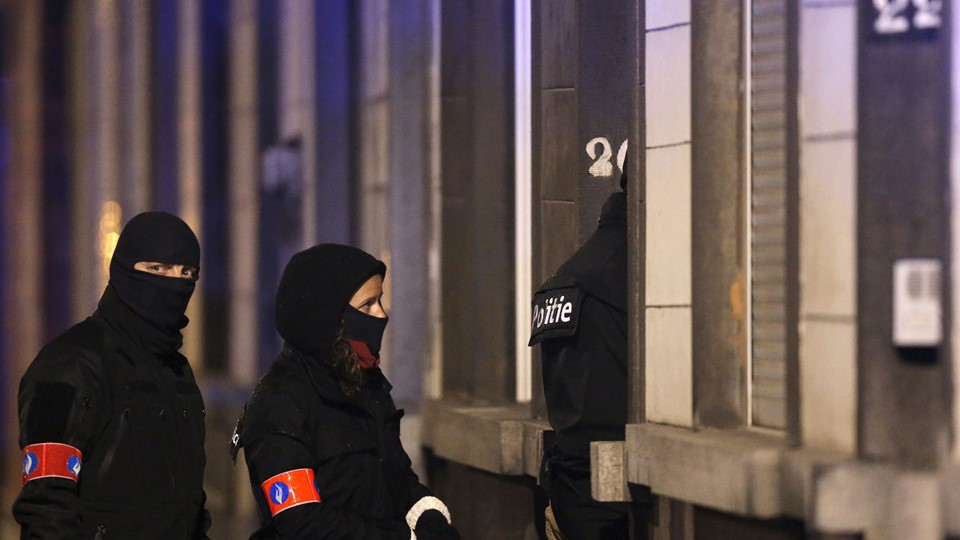 Masked Belgian police secure the entrance to a building in Schaerbeek Foto: Reuters/Christian Hartmann