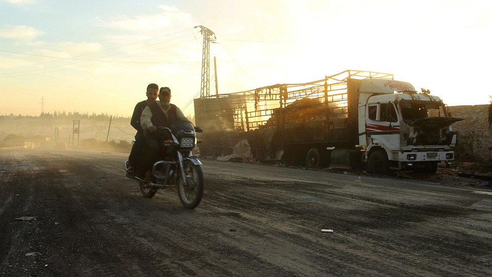 Men drive a motorcycle near a damaged aid truck after an airstrike on the rebel held Urm al-Kubra town Foto: Reuters/Ammar Abdullah