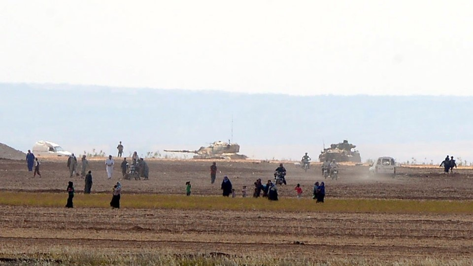 Syrian civilians, with Turkish Army tanks in the background, walk through the Turkish border as they are pictured from a village in Kilis province Foto: Reuters/Styringer