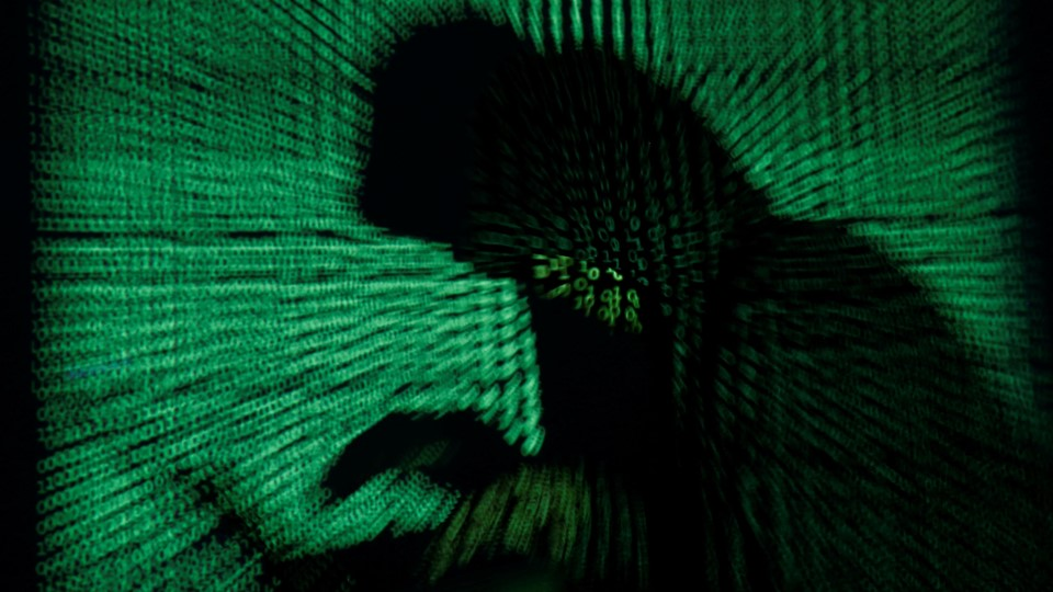 Hooded an holds laptop computer as cyber code is projected on him in this illustration picture Foto: Reuters/Kacper Pempel