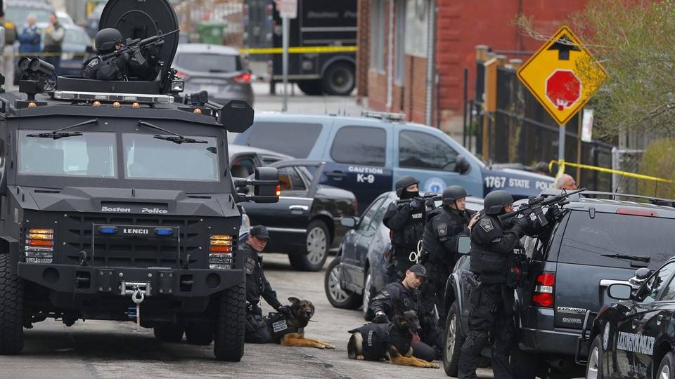 Police officers take position during a search for the Boston Marathon bombing suspects in Watertown, Massachusetts April 19, 2013. Police on Friday killed one suspect in the Boston Marathon bombing during a shootout and mounted a house-to-house search for a second man in the suburb of Watertown after a bloody night of shooting and explosions in the city's streets. REUTERS/Brian Snyder (UNITED STATES - Tags: CRIME LAW ANIMALS TPX IMAGES OF THE DAY)