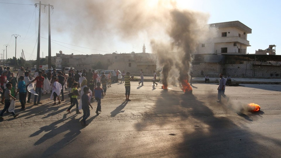 People gather near burning tyres during a demonstration against forces loyal to Syria's President Bashar al-Assad and calling for aid to reach Aleppo near Castello road in Aleppo Foto: Reuters/Abdalrhman Ismail