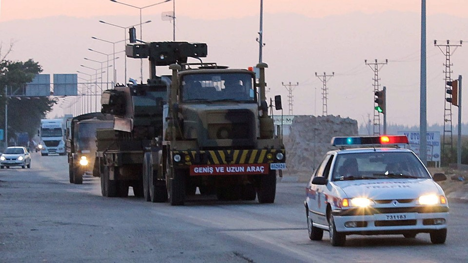 epa03285587 A photo made available 28 June 2012 shows part of a Turkish military convoy, including trucks apparently loaded with missile batteries arriving in the Hattay central disctrict of the coastal town of Iskenderun, 26 June 2012, on their way to be deployed near the the Syrian border some 50 kilometers away. Turkey has begun moving convoys of military vehicles and missile launchers into areas on its border with Syria, according to media reports on 28 June 2012. EPA/CEM GENCO / ANADOLU AGENCY EDITORIAL USE ONLY/NO SALES/NO ARCHIVES